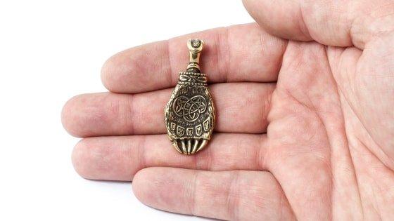 Фотография бронзовой лапы Велеса на руке.